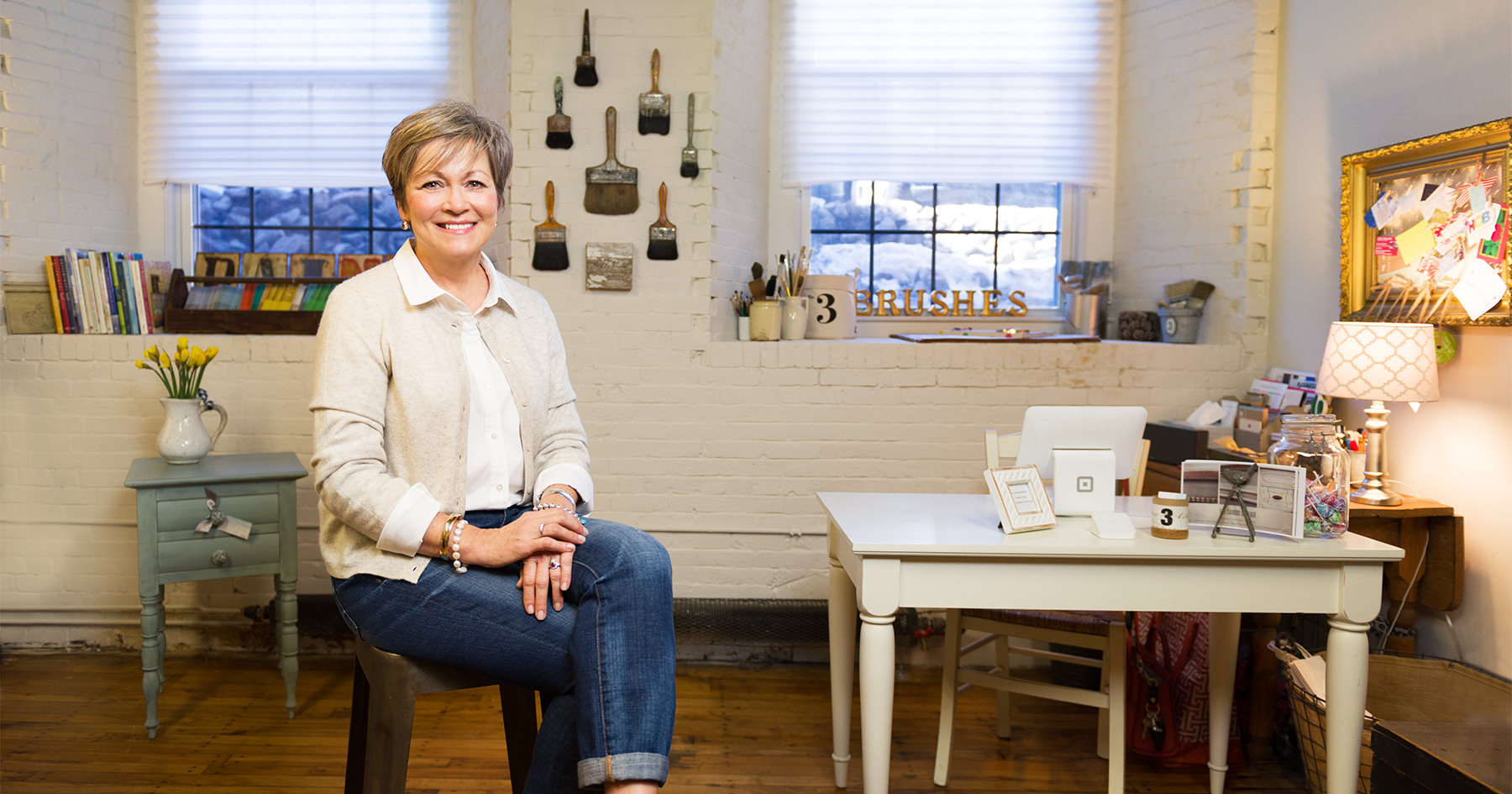 Donna Thomson, photographed by Portland Headshot, standing among some of the hand painted furniture that she creates and sells at the Pepperell Mill Campus.
